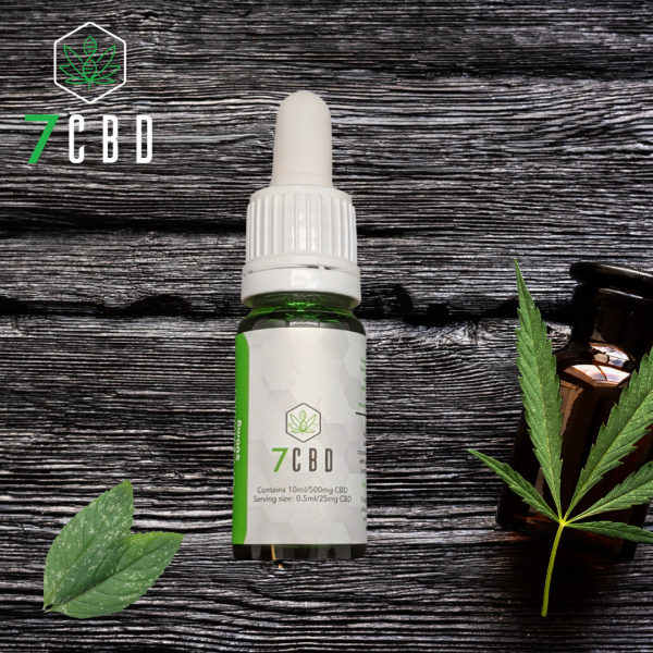 500mg CBD oil tincture lying on a woodern table with peppermint leaves on the left and a brown tincture with a cannabis leaf resting on it to the right
